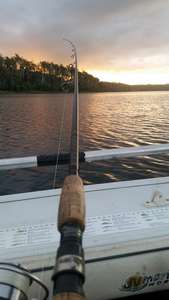A fishing rod against the side of a boat looking toward a beautiful sunrise over Four Springs Lake