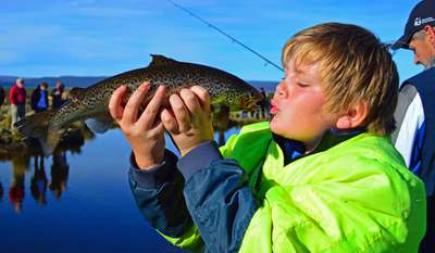 A junior angler at Trout Weekend, very happy with his catch of a fine rainbow trout.